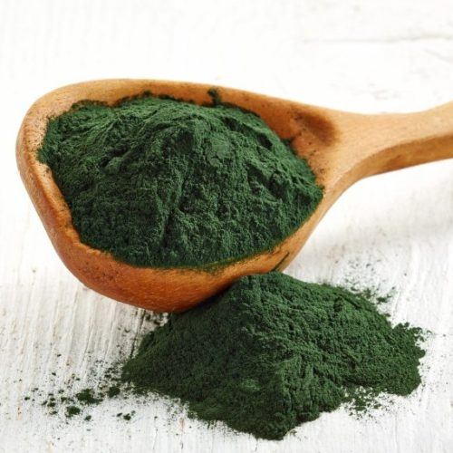 Wooden spoon of spirulina algae powder on wooden background