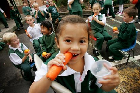 Primary school students snack on fruit and vegetables as part of the Sip and Crunch program.
