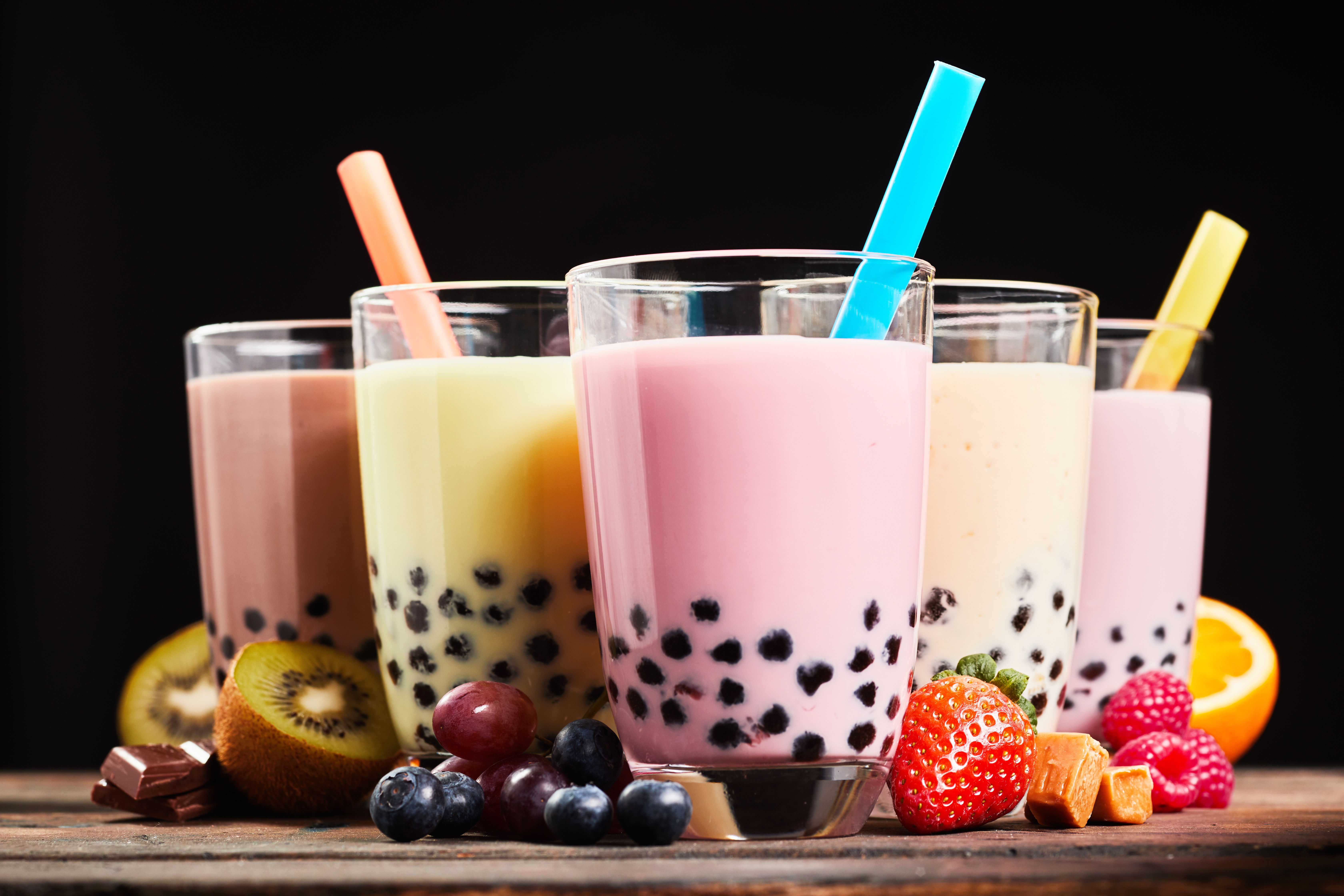 Glasses of refreshing milky boba or bubble tea with assorted fresh fruit ingredients, chocolate and caramel candy used as flavoring, low angle side view